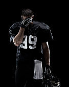 Waist up / one man only / one person / front view of adult handsome people caucasian young men / male american football player / athlete standing in front of black background wearing helmet / sports helmet who is lost and using sports ball