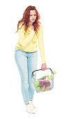 Beautiful young woman holding a shopping basket