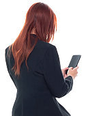 Rear view / back / one person / waist up / portrait of 20-29 years old adult beautiful redhead / long hair caucasian female / young women businesswoman / business person wearing businesswear / a suit and holding mobile phone / using smart phone