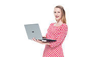 Looking at camera / one person / front view / waist up of 18-19 years old adult beautiful caucasian female / young women teenage girls standing wearing dress who is smiling / happy / cheerful / cool attitude who is working and using laptop / computer