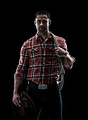 Waist up / one man only / one person of adult handsome people caucasian young men / male cowboy standing in front of black background wearing lumberjack shirt / plaid shirt / button down shirt / shirt / jeans / pants / cowboy hat / hat and using rope