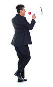 Full length / rear view of 20-29 years old adult handsome people / tall person curly hair african ethnicity / african-american ethnicity male / young men businessman / business person walking in front of white background wearing a suit