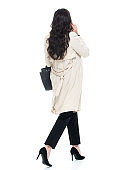 Rear view / back / full length / one person of 40-44 years old adult beautiful brown hair / long hair caucasian female / young women business person / businesswoman / manager walking wearing businesswear / a suit who is talking / overworked