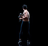 Full length / one man only / one person of 30-39 years old handsome people black hair chinese ethnicity / east asian ethnicity male / young men standing / exercising in front of black background wearing sports shoe / leggings / black color / back lit