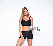 Waist up of 20-29 years old adult beautiful caucasian female / young women standing / exercising in front of white background wearing sports clothing / sports bra / shorts / running shorts who is smiling / happy / cheerful