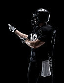 Waist up / one man only / one person / side view / profile view of adult handsome people caucasian young men / male american football player / athlete / presenter standing in front of black background wearing helmet / sports helmet / presenting