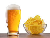 Glass of light beer and chips on bar counter