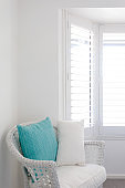 White Wicker Chair with Blue Cushion In Clean White Bedroom - Home Decor