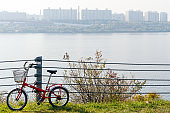 Red bicycle attached to the fence with a river and city view background.