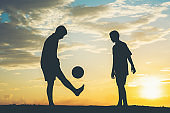 Silhouette of children play soccer football
