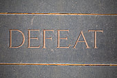 The word 'DEFEAT' carved/ chiselled into cracked dark slate/stone.