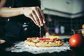 Close up of woman hand putting oregano over tomato and mozzarella on a pizza. Cooking concept