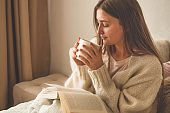 Cozy Autumn winter evening. Woman drinking hot tea and reading book