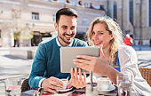 Young couple sitting in the cafe and having fun with tablet. Dating, relationships, love, romance, lifestyle, technology