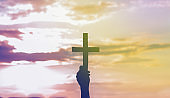 Teenager Girl holding a the cross in hand during beautiful sunset. Hands folded in prayer concept for faith, spirituality and religion