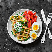 Crispy potato waffles with sour cream and green onions, smoked trout, boiled egg - delicious breakfast, snack, brunch on a dark background, top view