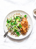 Quinoa, baked chicken breast, avocado, cheese, cilantro bowl on light background, top view. Healthy eating concept