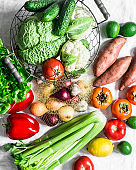 Fresh organic vegetables, fruits on a light background, top view. Healthy diet food concept. Sweet potato, savoy cabbage, sweet peppers, celery, cucumbers, tomatoes, persimmon - delicious vegetarian food