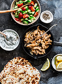 Ingredients for greek chicken gyros - fried chicken, tomato cucumber salad, tzatziki sauce and flatbread on a dark background, top view. Flat lay