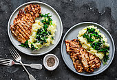 Roast pork with mashed potatoes and spinach - comfort winter meal on a dark background, top view