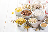 Selection of whole grains in white bowls - rice, oats, buckwheat, bulgur, porridge, barley, quinoa, amaranth,