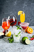 Selection of refreshing summer drinks - mojito, sangria, mimosa, aperol, martini, rustic background