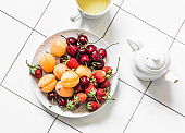 Delicious healthy dessert - fresh ripe fruits and berries strawberries, apricots, cherries and green tea on a light background, top view