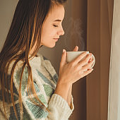 Woman with cup of hot drink by the window. Looking at window and drink tea. Good morning with tea