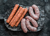 Raw uncooked turkey and spicy smoked paprika pork homemade sausages on a cutting board on dark background, top view. Food ingredients