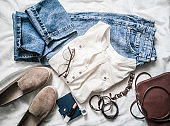 Summer women's fashion clothes set - mom's jeans, suede sneakers, cotton t-shirt, leather bag, bracelets, lipstick on a light background, top view. Beauty, fashion concept. Flat lay