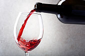 Red wine is poured into a glass from a bottle. Light background.