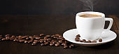 A cup of coffee and coffee beans on the table. Black background. Copy space of your text. Banner.
