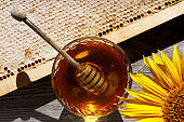 Fresh sweet honey in a glass bowl and honey honeycombs on an old wooden table.