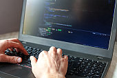 Programmer coding on laptop. Coder hands typing program code