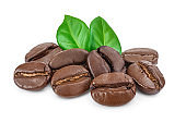 Heap of roasted coffee beans with leaves isolated on white background.