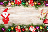 Christmas frame made of fir branches decorated with balls, Santa Claus on a light wooden background