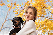 teenager girl holding her dachshund dog in her arms outdoors