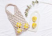Handmade shopping macrame bag with lemon on the white cotton background