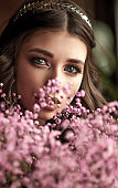Beautiful brunette girl with a bouquet of flowers close-up