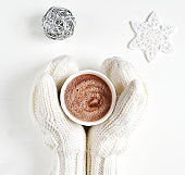 Woman Hands Holding Cup with Hot Chocolate Christmas New Year Concept White Mittens Marshmallow Winter Snow Flat Lay Style White Background