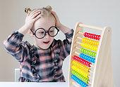 Caucasian little girl with round glasses. Little teacher. Funny glasses humor. Retro style