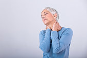 Close up of sad senior lady with neckache. Senior woman with chronic pain syndrome fibromyalgia suffering from acute neckaches. Senior woman suffering from neck pain