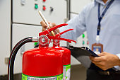 Engineer are inspection Fire extinguisher in fire control room for emergency, rescue and safety Concept.