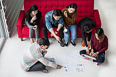 Group Of Students Teamwork Brainstorming  in University. young business people Start up Team Meeting sitting on floor and red sofa