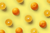 Fruit pattern of fresh orange slices on yellow background. Top view. Copy Space. Pop art design, creative summer concept