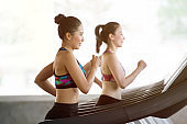 group of young asian people running on treadmills in sport gym . two fitness woman runner on running machine in morning time . workout .training . exercise. healthy lifestyle .