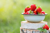 Plate with juicy strawberries on wooden stands on the background of green grass.