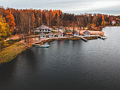 Aerial view of forest and blue lake. Sauna house by the lake shore. Wooden pier with fishing boats. St. Petersburg, Russia.