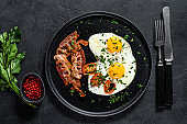 Fried eggs with bacon. Classic Breakfast at the hotel. Black background. Top view