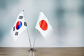 South Korean and Japanese flag standing on the table